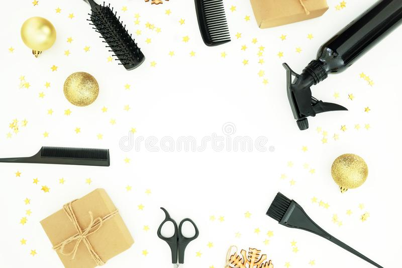 Composición del marco del peluquero de la Navidad con el espray, los peines, las tijeras y la caja de regalo con las bolas en el  imagen de archivo