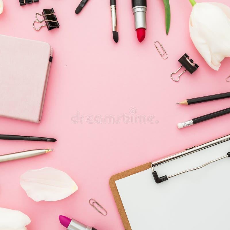 Composición del negocio con el tablero, los tulipanes, los cosméticos y el accesorio en fondo rosado Visión superior Endecha plan imagen de archivo