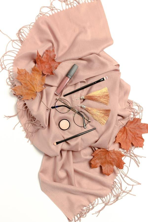 Composición del otoño con las hojas de arce secas, la bufanda marrón, los vidrios, los cosméticos de las mujeres y los accesorios fotografía de archivo