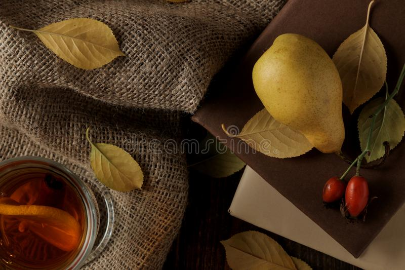 Composición del otoño con las peras, los libros y el escaramujo calientes del té imagen de archivo libre de regalías