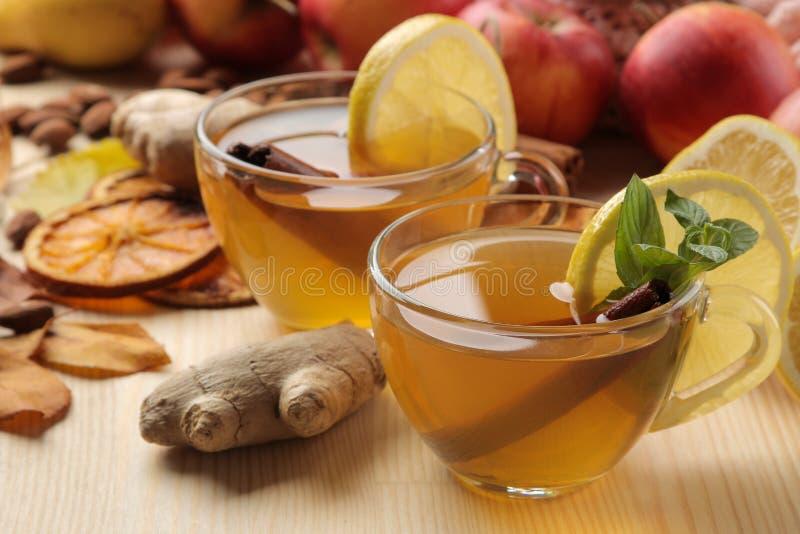 Composición del otoño con té caliente, frutas y hojas amarillas en una tabla de madera natural foto de archivo libre de regalías