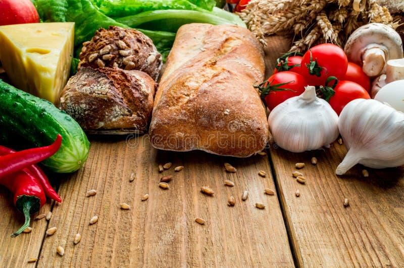 Composición del pan, tomates, ajo, pepino, queso, pimienta, verdes, setas en un tablero de madera imagenes de archivo