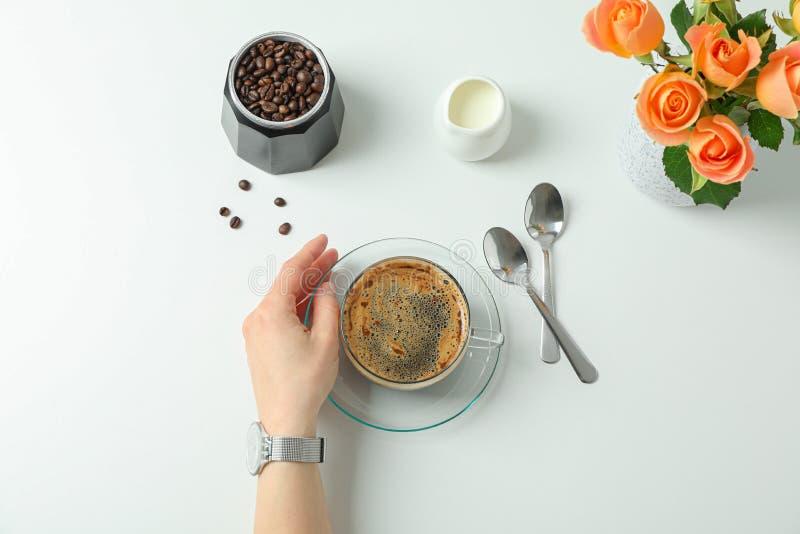 Composición del tiempo del café con la mano femenina en el fondo blanco, visión superior foto de archivo