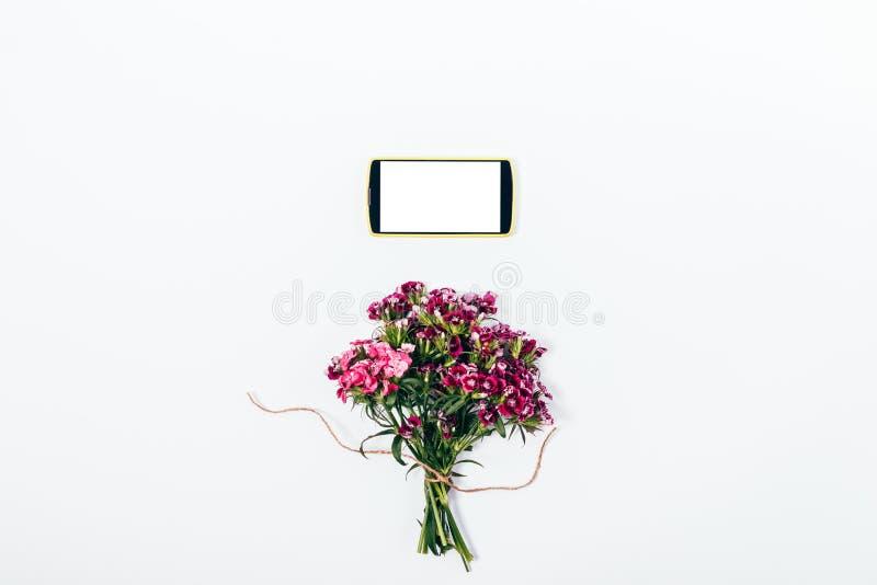 Composición del verano de la visión superior del ramo y del teléfono elegante foto de archivo libre de regalías