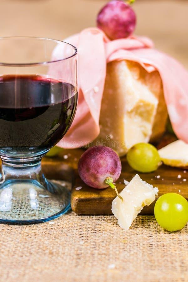 Composición del vidrio de vino rojo, de uva, de queso y de salami en un tablero de madera y una lona fotografía de archivo