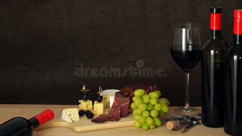 Composición del vino tinto con queso, el jamón y las uvas fotos de archivo libres de regalías