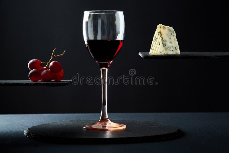 Composición del vino tinto en vidrio al lado del queso verde y de la uva en fondo negro fotos de archivo libres de regalías