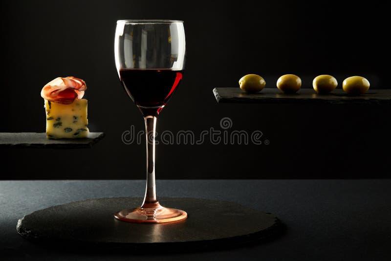 Composición del vino tinto en vidrio y pedazos de prosciutto y queso y aceitunas en fondo negro imagen de archivo libre de regalías