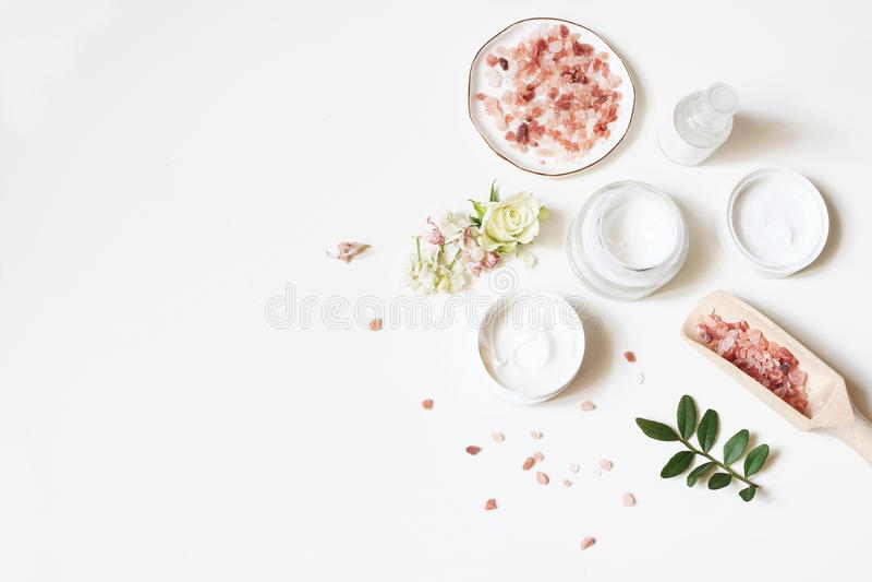 Composición diseñada de la belleza Crema de piel, botella del tonicum, flores secas, rosa y sal Himalayan en el fondo blanco de l fotografía de archivo
