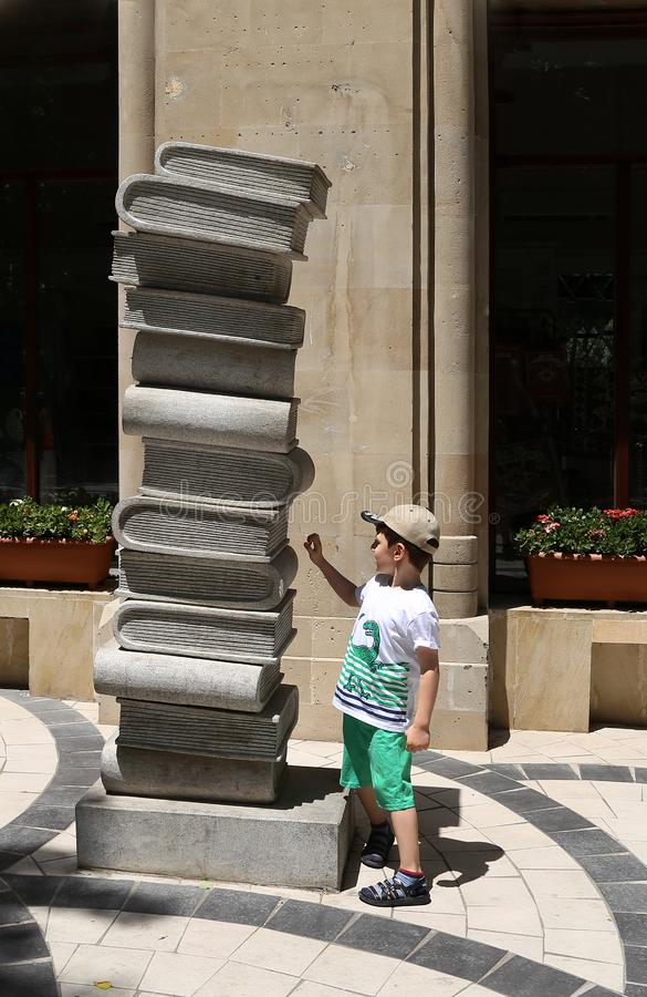 Composición escultural bajo la forma de pila de libros cerca de una librería en el cuadrado de la fuente adentro imágenes de archivo libres de regalías