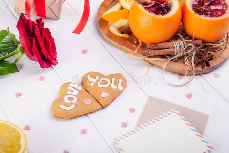 Composición festiva con las galletas en la forma del corazón con el amor que usted redacta, que subió, inusual servido en vino re imagenes de archivo