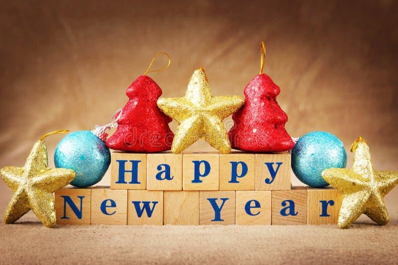 Composición festiva de la Feliz Año Nuevo con un texto dispuesto de cubos de madera y de decoraciones coloridas fotografía de archivo