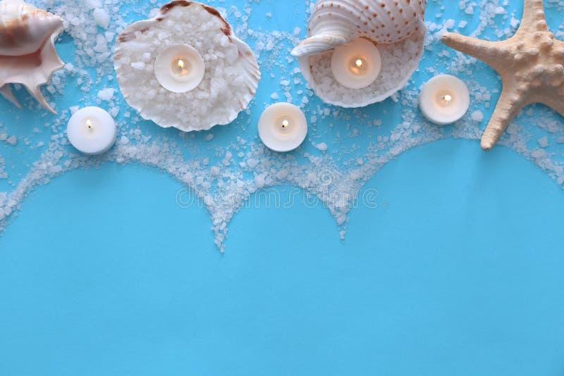 Composición hermosa con las velas y las conchas marinas ardientes en fondo del color fotografía de archivo