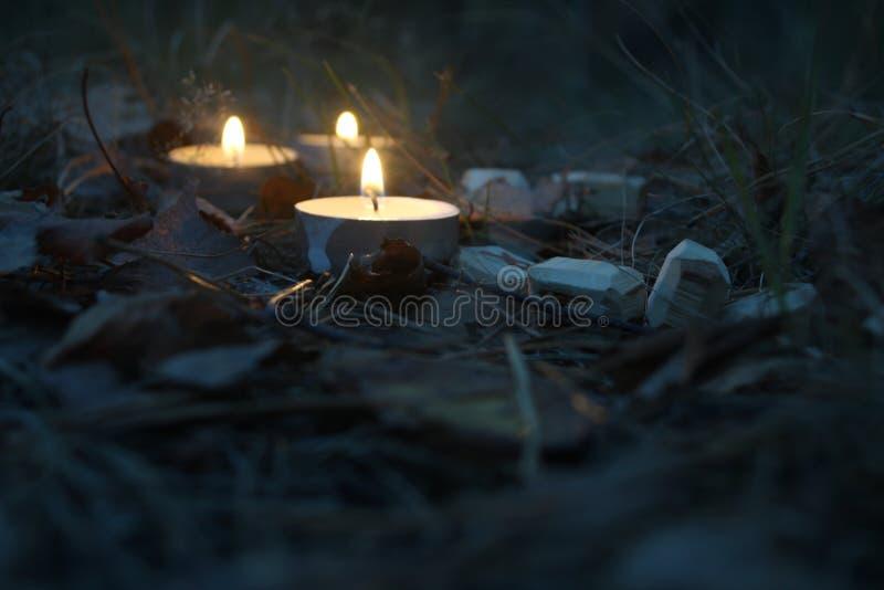 Composición hermosa de Halloween con las runas y las velas en la hierba en ritual oscuro del bosque del otoño fotografía de archivo libre de regalías