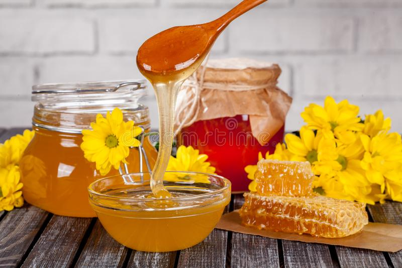 Composición hermosa de los productos de la miel, de la miel, de panales, del perga y de las flores del verano en una tabla de mad fotos de archivo