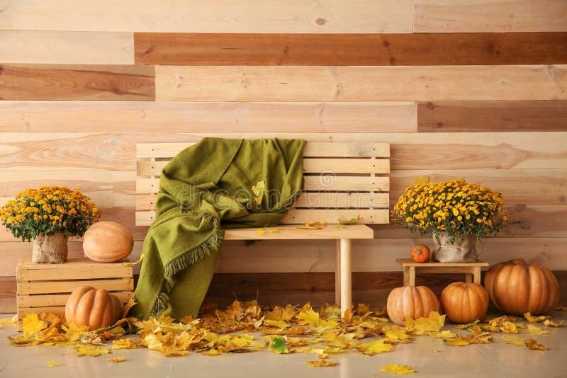 Composición hermosa del otoño con el banco, las calabazas y las hojas cerca de la pared de madera fotos de archivo libres de regalías