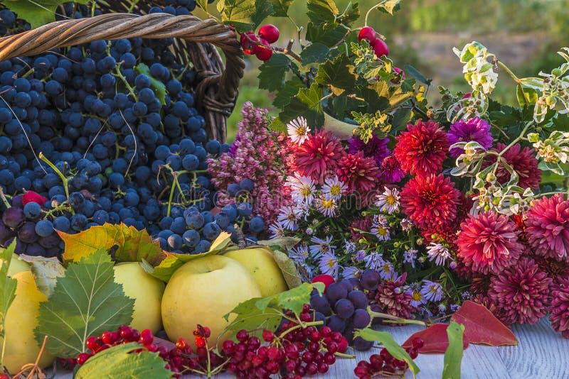 Composición hermosa del otoño con las frutas y el manojo de flores maduros foto de archivo libre de regalías