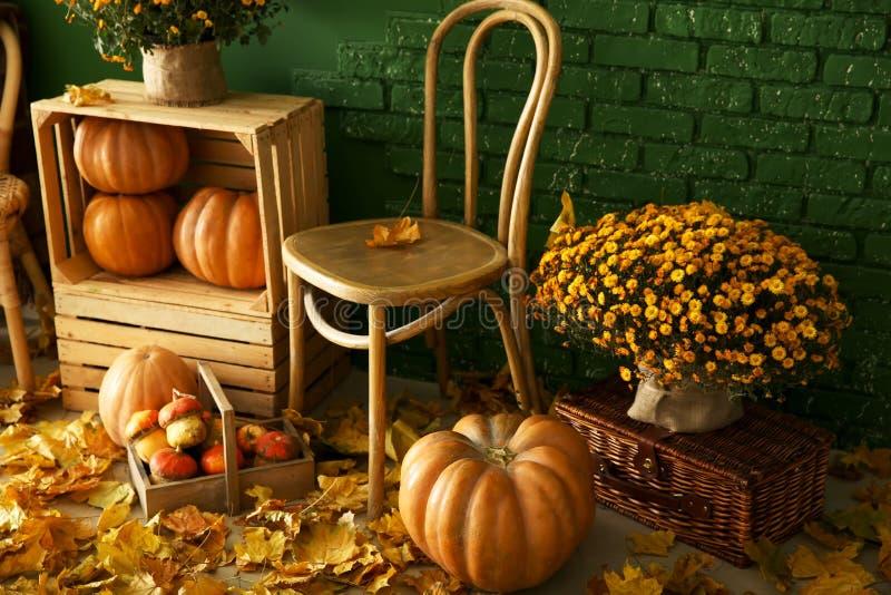 Composición hermosa del otoño con muebles, calabazas y hojas de madera cerca de la pared del color fotos de archivo