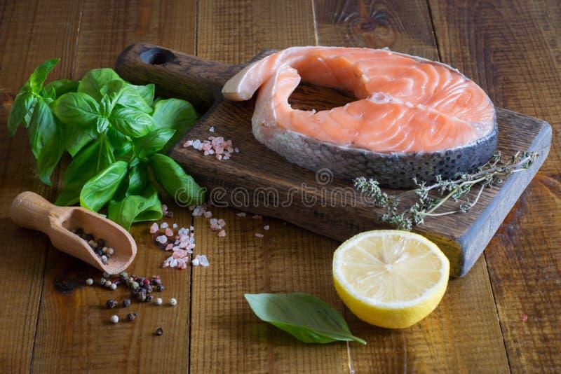 Composición hermosa: filete de color salmón en una tabla de cortar, un pedazo de limón, albahaca fresca, especias, tomillo fotografía de archivo libre de regalías