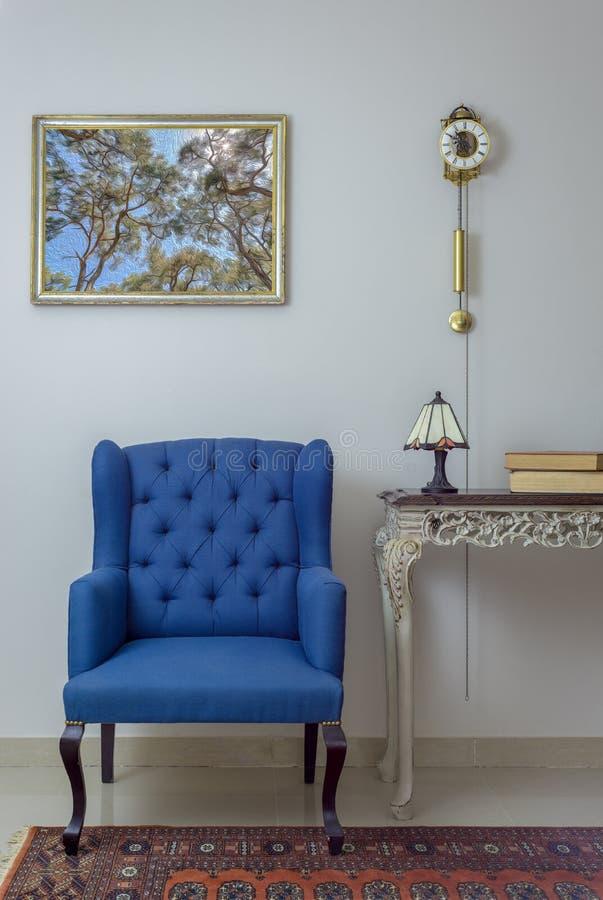 Composición interior de la butaca azul retra, de la tabla del vintage, de la lámpara de mesa, de libros, y del reloj de péndulo b fotos de archivo
