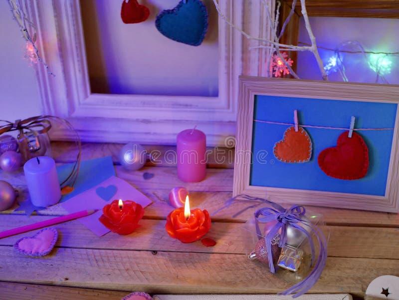 Composición interior festiva estacional de velas encendidas, decoración, marcos de madera, lámparas decorativas, corazones del fi fotos de archivo libres de regalías