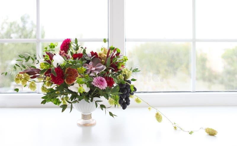 Composición inusual con las flores suculentas, uva, higo a de la boda imagen de archivo