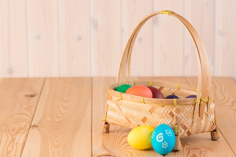 composición lacónica de Pascua - cesta con los huevos coloreados imagen de archivo
