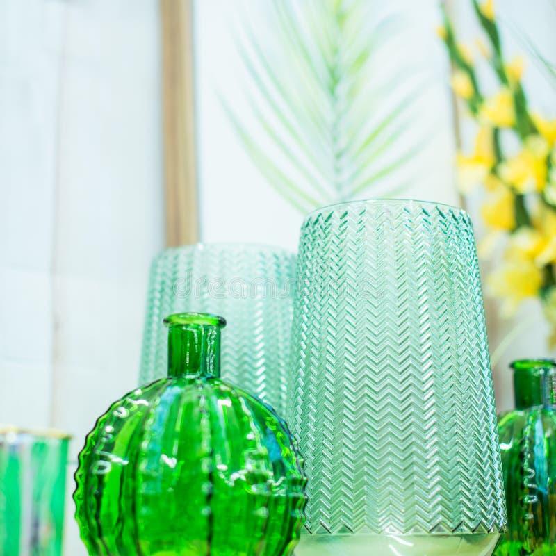 Composición más cercana de jarrones de vidrio verde claro, marco de afiche con hoja tropical sobre fondo blanco. Escandinavo mod fotos de archivo
