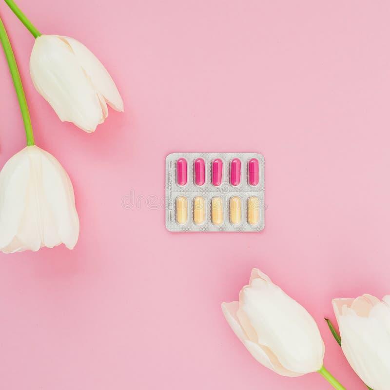 Composición médica con las píldoras de las vitaminas y las flores blancas en fondo rosado Endecha plana, visión superior foto de archivo