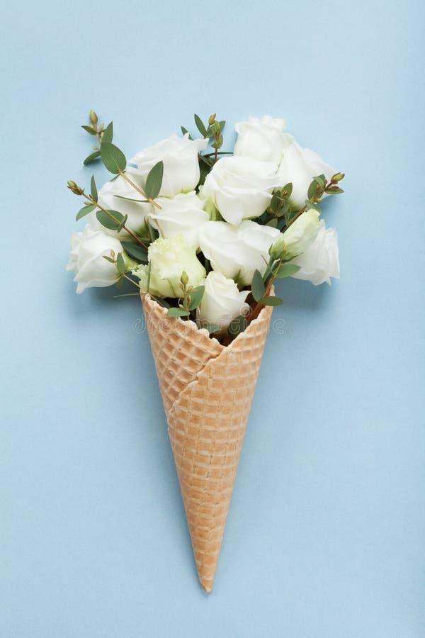 Composición mínima con el helado creativo de flores hermosas en la visión superior de papel en colores pastel azul estilo plano d imagen de archivo