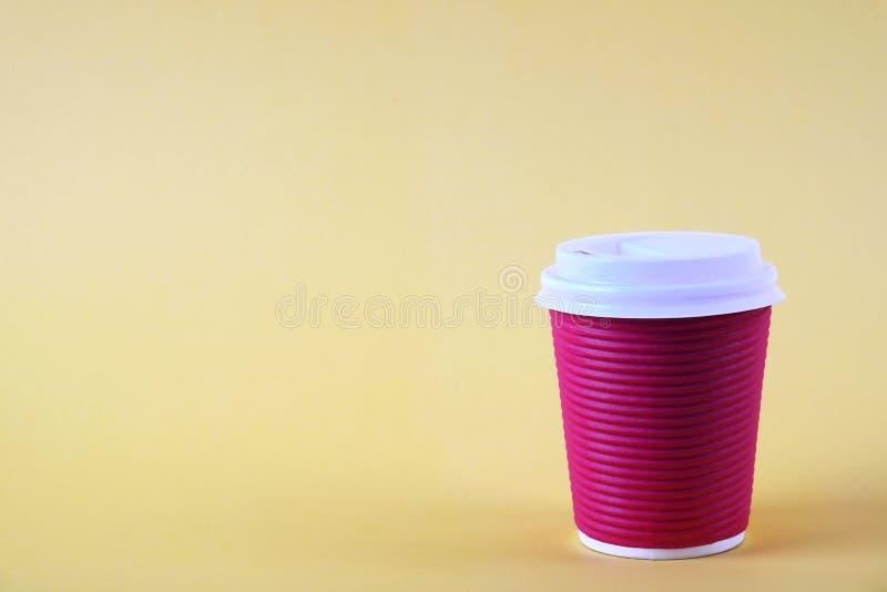 Composición mínima simplista colorida con la taza de café del papel de prueba de calor Saque la taza del té con el casquillo plás foto de archivo libre de regalías