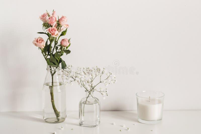Composici?n minimalistic elegante con las rosas y las flores del gypsophila en fondo de la pared de la tabla Maqueta de la vista  foto de archivo