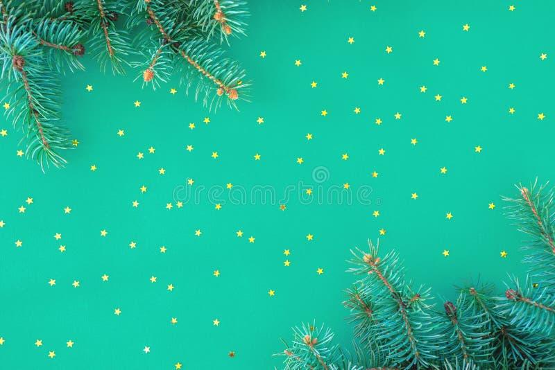 Composición navideña con bordes de ramas de abeto y estrellas doradas dispersas en el fondo de la menta imágenes de archivo libres de regalías