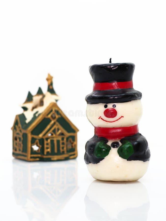 Composición navideña, muñeco de nieve cera, una pequeña casa imagenes de archivo