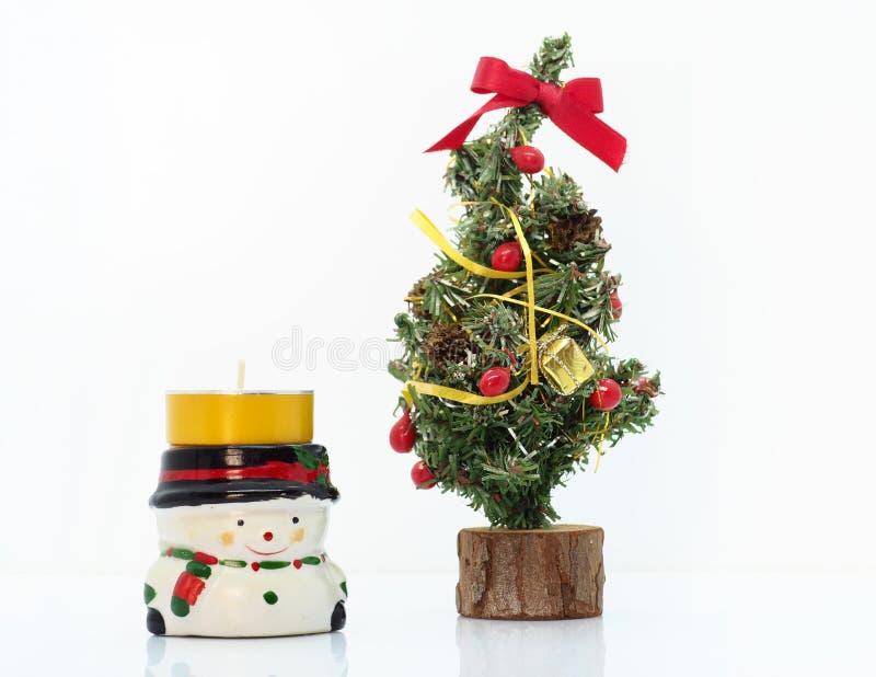 Composición navideña, muñeco de nieve y un pequeño árbol de Navidad foto de archivo