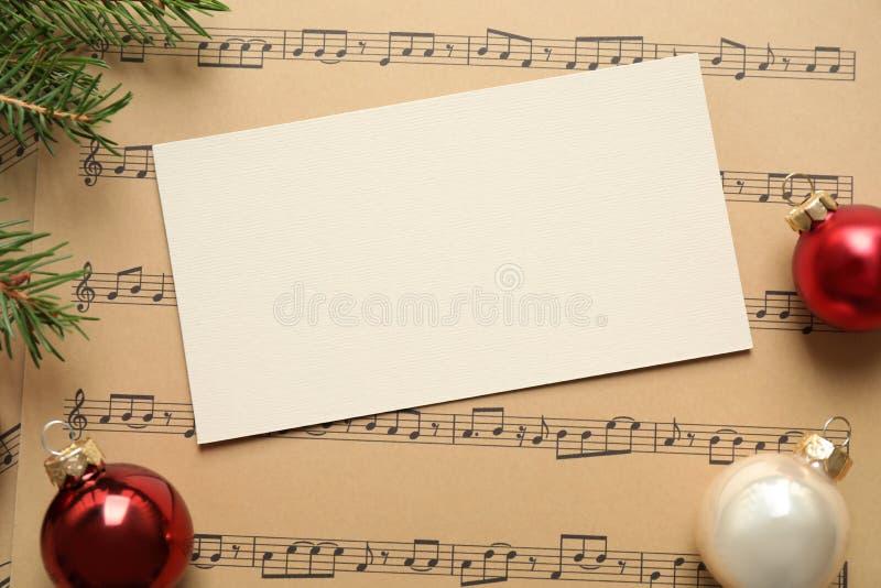 Composición plana con decoraciones navideñas y tarjeta en blanco en hojas de música fotografía de archivo