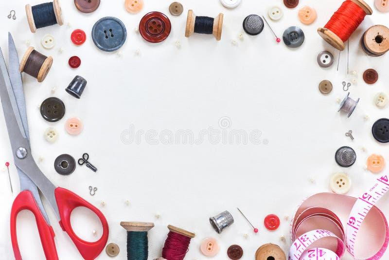 Composición plana con las tijeras y las fuentes de costura en el fondo blanco Espacio para el texto fotos de archivo libres de regalías