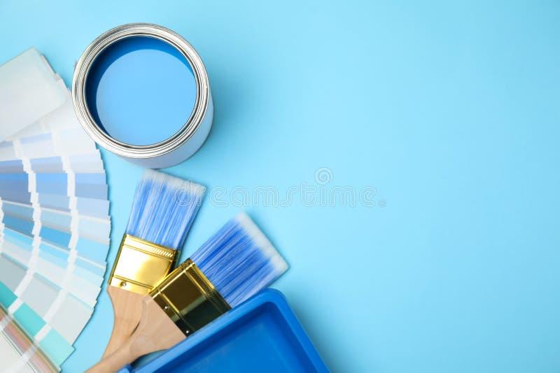 Composición plana con lata de pintura, cepillo y herramientas de renovación en fondo azul fotos de archivo libres de regalías