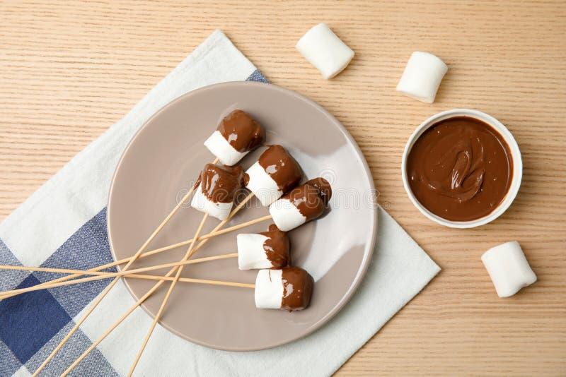 Composición plana de la endecha con la 'fondue' de chocolate en cuenco y melcochas fotografía de archivo libre de regalías