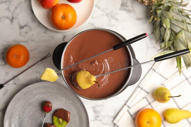 Composición plana de la endecha con la 'fondue' de chocolate en pote y frutas fotos de archivo