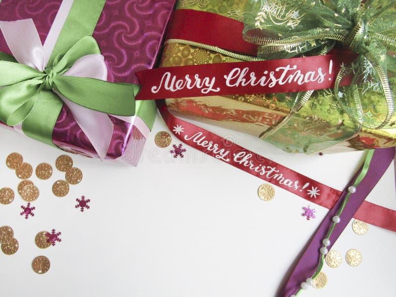 Composición plana de la endecha con las actuales cajas adornadas con las cintas de satén y caligrafía de la Feliz Navidad stock de ilustración
