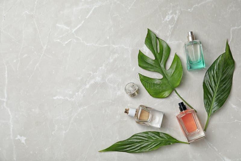Composición plana de la endecha con las botellas de perfume imagenes de archivo