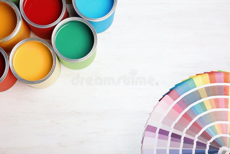 Composición plana de la endecha con las latas y la paleta de colores de la pintura en fondo de madera ilustración del vector