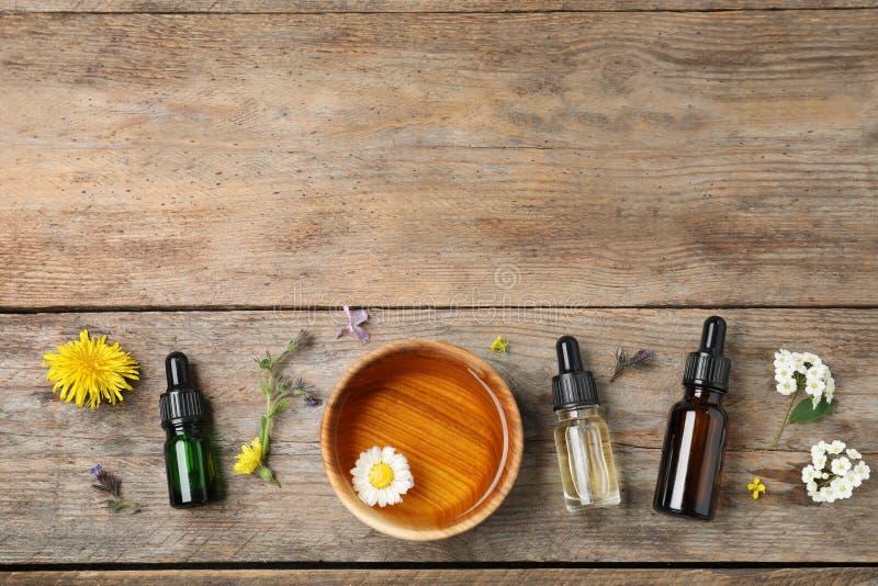 Composición puesta plana con aceites esenciales, el cuenco y las flores en la tabla de madera imagen de archivo