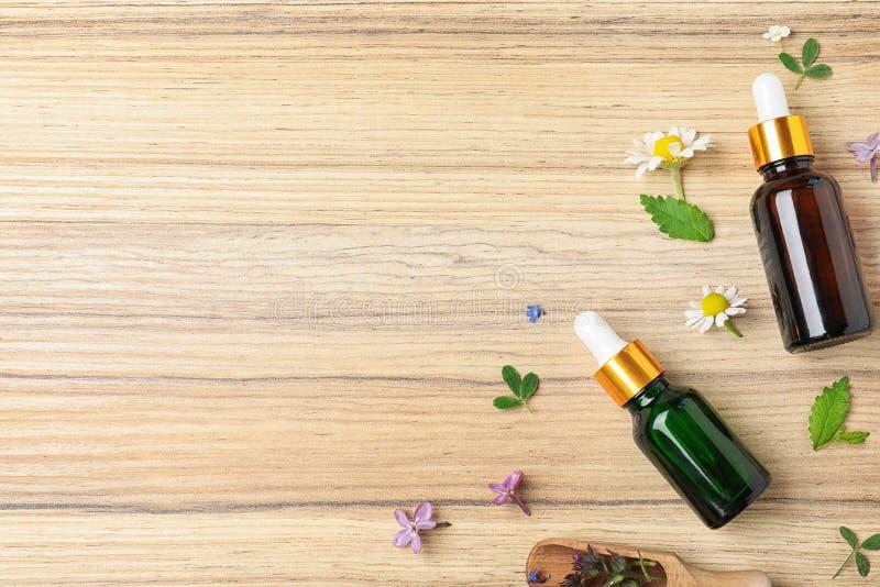 Composición puesta plana con aceites esenciales, la cucharada y las flores en la tabla de madera imagenes de archivo