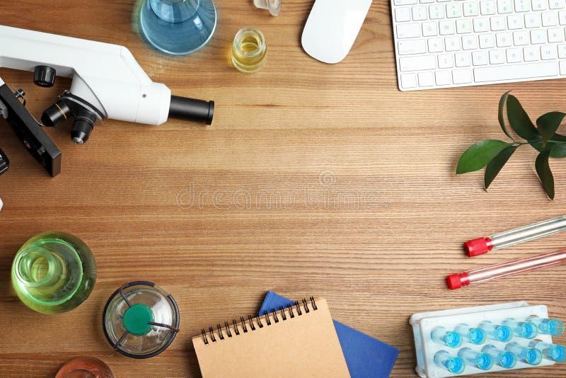 Composición puesta plana con cristalería, el microscopio y el espacio de laboratorio para el texto en fondo de madera química fotos de archivo libres de regalías