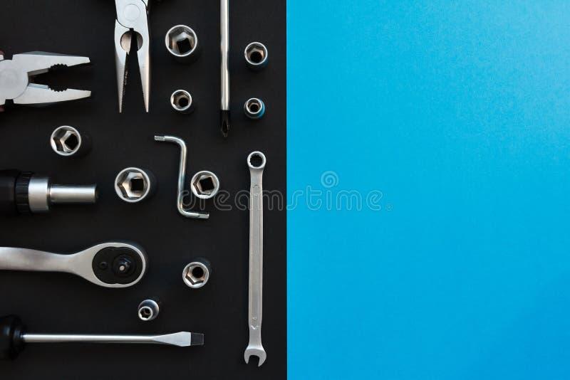 Composici?n puesta plana con diversas herramientas de la construcci?n en fondo negro y azul Vista superior de las herramientas de fotografía de archivo libre de regalías