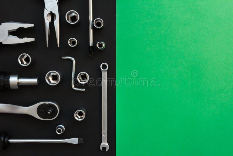 Composici?n puesta plana con diversas herramientas de la construcci?n en fondo negro y verde Vista superior de las herramientas d fotos de archivo