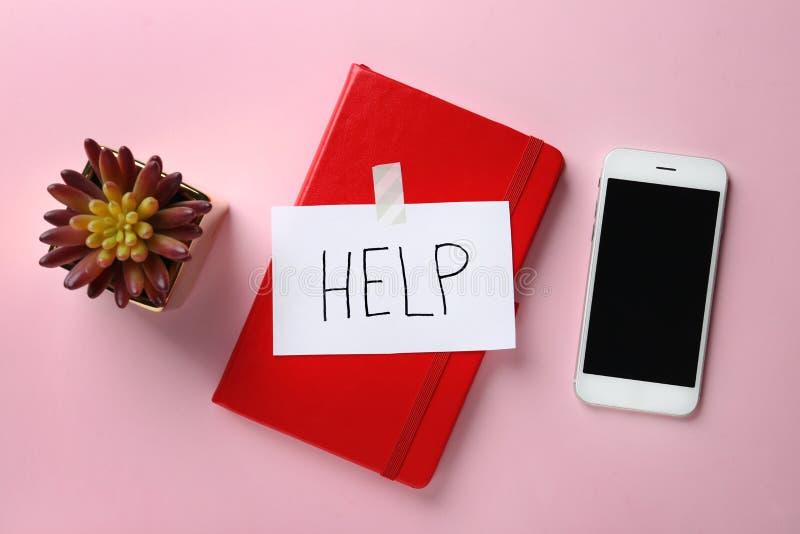Composición puesta plana con el cuaderno, la palabra AYUDA y el smartphone en fondo del color fotografía de archivo