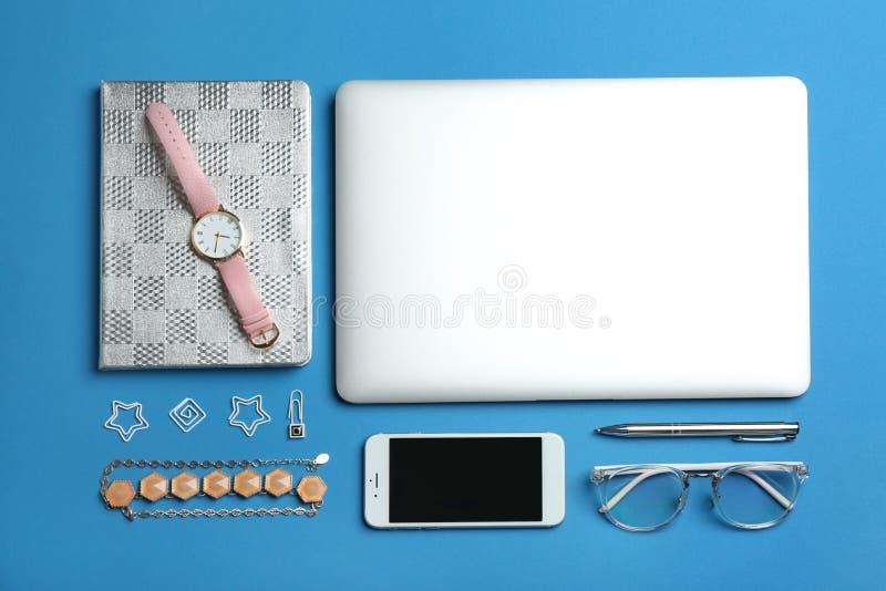 Composición puesta plana con el ordenador portátil, el smartphone y los accesorios en fondo del color fotografía de archivo